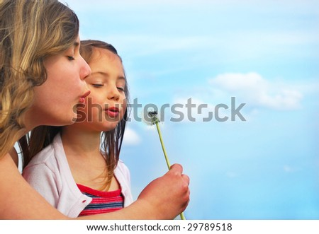 Sisters blowing dandelion on a meadow and have fun
