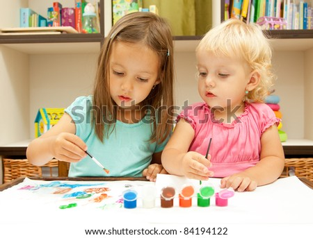 sisters drawing with colored paint