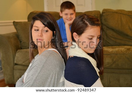 sisters in an argument as the instigator watches from behind