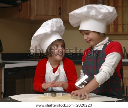 Sisters in aprons and chef's hats making cookies for Christmas.