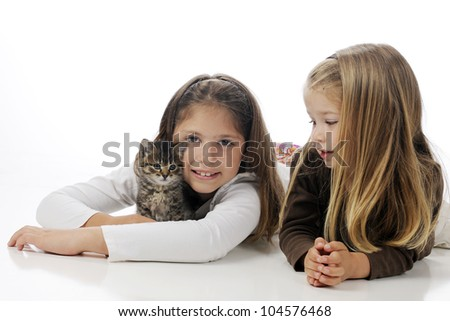 Sisters laying on the floor cuddling their kitty.  On a white background.