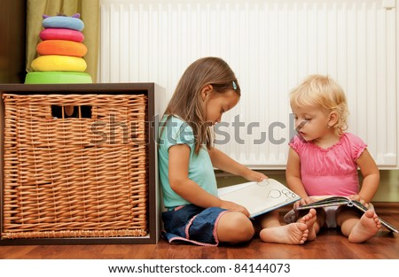 sisters on the floor reading the book
