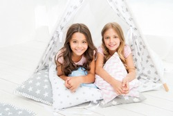 Sisters or best friends spend time together lay in tipi house. Girls having fun tipi house. Girlish leisure. Sisters share gossips having fun at home. Pajamas party for kids. Cozy place tipi house.