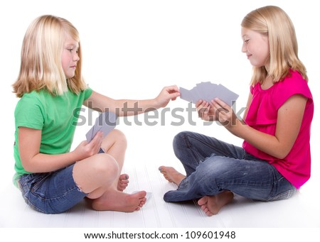sisters or friends playing cards, white background