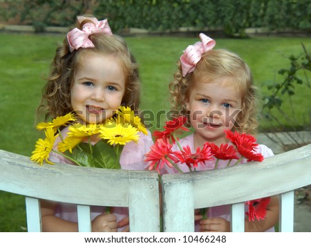 Sisters stand by white, wooden garden gate.  They have picked bouquets for their mom.