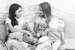 Sisters unite. Little sisters play toys in bed. Small sisters relax before nap time. Adorable sisters or friends in bedroom. Sisterhood and family. Friendship. Future is female