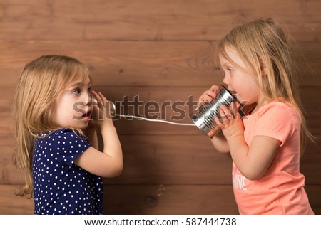 Sisters using old tin can telephone to talk