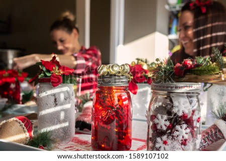 Sisters wearing red plaid shirts in making Christmas crafts in their kitchen with snow painted jars, pine cones, holly and poinsettias.