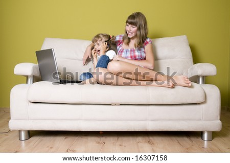 Sisters with laptop on sofa