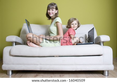 Sisters with laptops on sofa