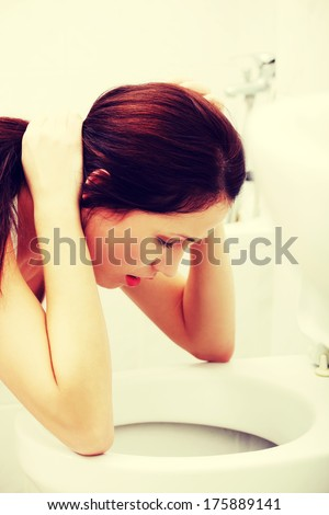 Site view of a voimiting woman in the bathroom in the morning.