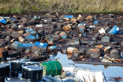 Site with chemically contaminated waste. Barrels with toxic waste in water.  Earth pollution problem