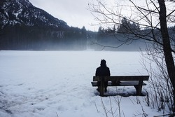 Sitting alone on the bench by woods.