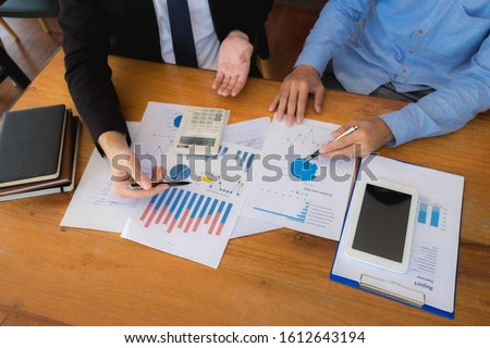Sitting and working, consulting and suggesting work, checking work reports with a calculator in a business office.