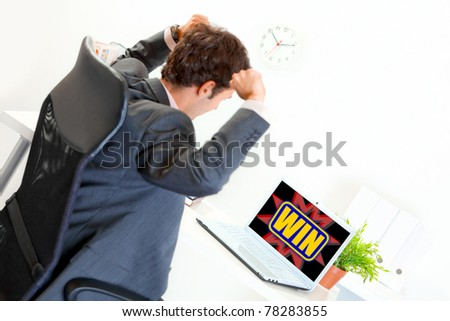 Sitting at office desk excited modern businessman with hands raised up looking on laptop