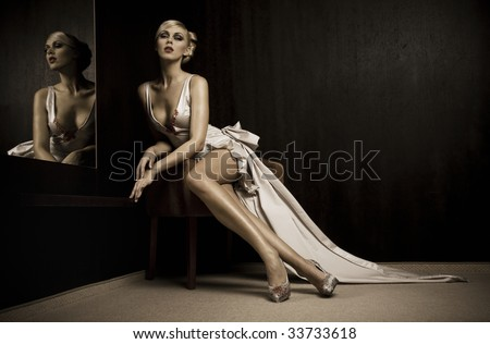 Sitting beautiful woman beside mirror - stock photo