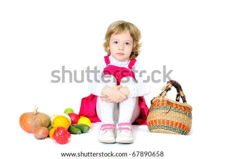 sitting blonde little girl with vegetables over the white