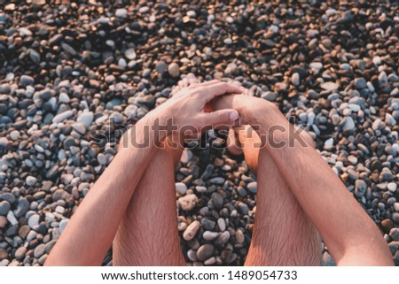 Sitting by the sea on a rocky beach, point of view shot. Male swimmer sits on pebble in sunset, snapshot style image