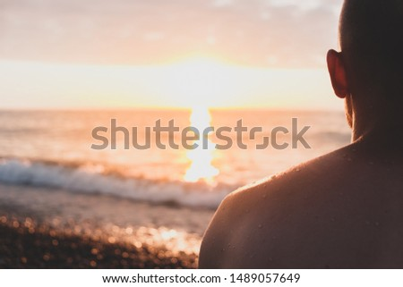 Sitting by the sea on a rocky beach, shot from behind the person. Male swimmer sits on pebble in sunset appreciating the sunset