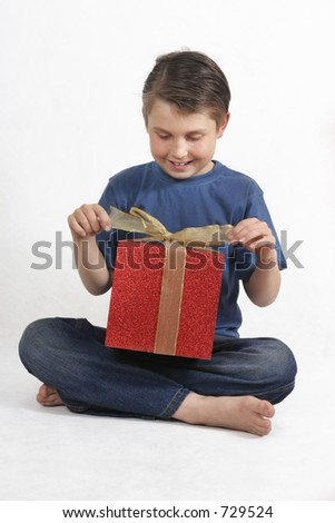 Sitting child in blue jeans and shirt opens up a bright red and gold present.  Suitable for christmas or birthdays.