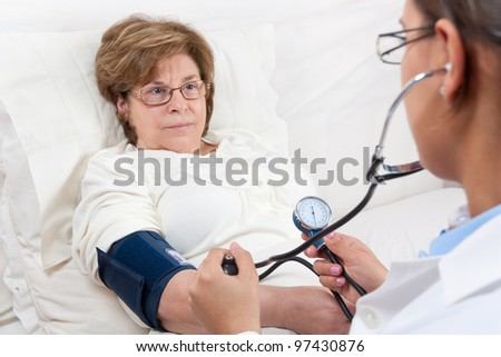 Sitting Doctor is measuring the Blood Pressure on a Senior Patient