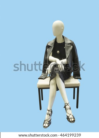 Shutterstock Sitting female mannequin wearing black dress and leather jacket, against blue background.  No brand names or copyright objects.