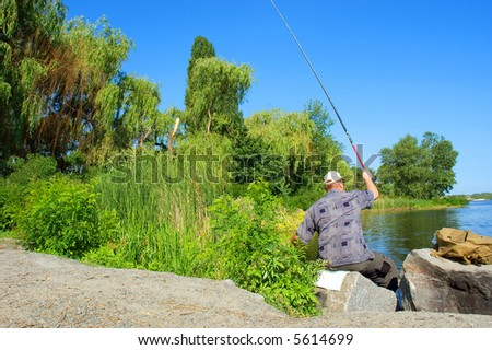 Sitting fisherman casts the rod  into morning river. Shot in June near Dnieper river, Ukraine.
