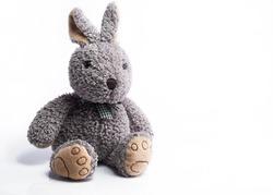 Sitting gray bunny rabbit toy white background