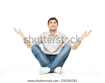 Sitting happy man with raised hands up isolated on white background.