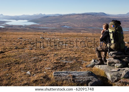 sitting Hiker with heavy backpack in Lapland