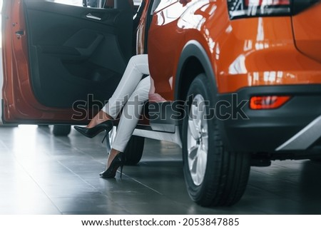 Sitting in the car. Woman in formal clothes is indoors in the autosalon.