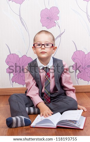 Sitting little boy with diary looks like a business man