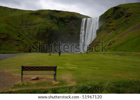 Sitting near the waterfall. Skogafoss waterfall. Skogar Southern Iceland