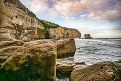 Sitting on a large boulder under the steep cliff  at Tunnel beach coastline watching the world go by