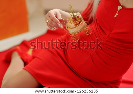 sitting on a red couch pregnant girl in a red dress with a toy