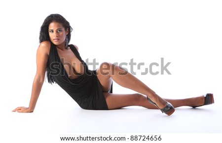 Sitting on floor a young beautiful african american fashion model wearing short black dress and stiletto heels, showing off long legs big boobs and cleavage.