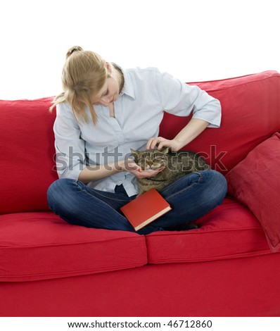 sitting on red sofa young woman with book strokes grey cat