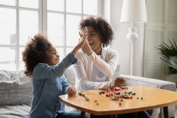 Sitting on sofa happy African little daughter gives high five to mother, family spend time together finish pastime activity, necklace jewelry from colorful wooden beads lie on table, hobby concept