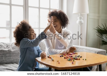 Sitting on sofa happy African little daughter gives high five to mother, family spend time together finish pastime activity, necklace jewelry from colorful wooden beads lie on table, hobby concept stock photo