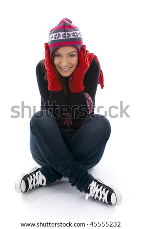 sitting on the floor smile girl from crossed legs in winter cap covers ears hands in mittens
