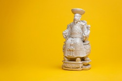 Sitting small emperor sculpture figurine in stately seat with white space. Studio souvenir still life against a seamless yellow background.