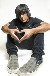Sitting teenage boy making heart symbol with hands