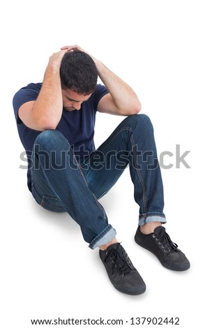 Sitting upset man with hands behind head on the floor on white background