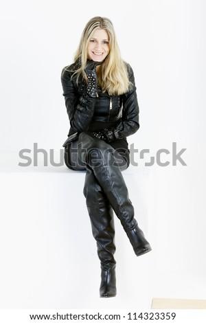 sitting woman wearing fashionable black boots - stock photo