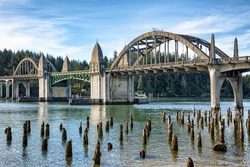 Siuslaw River Bridge from the Florence Marin withold wooden piles on foreground, Oregon USA