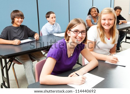 Six adolescent school children sitting at tables in class. - stock photo