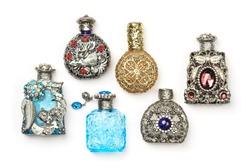 Six antique perfume glass richly ornate bottles, isolated on white.