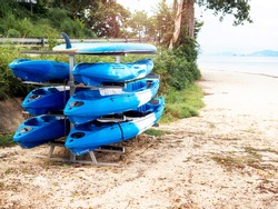 Six blue kayaks and a surfing paddle board stored in the outdoor racks on sand beach.