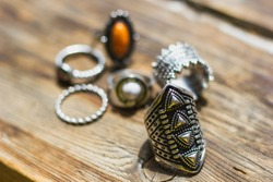 Six boho rings laying on the wooden texture