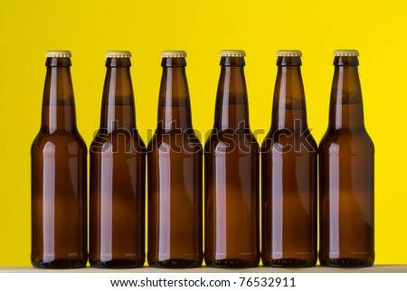 Six bottles of beer side by side on a yellow background